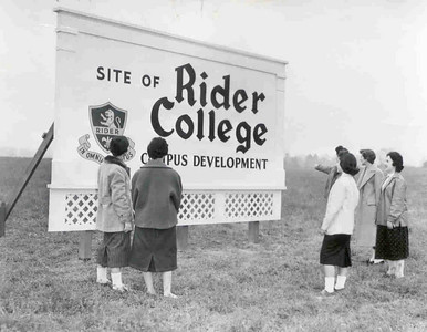 Coeds observing the sign during the groundbreaking ceremony.