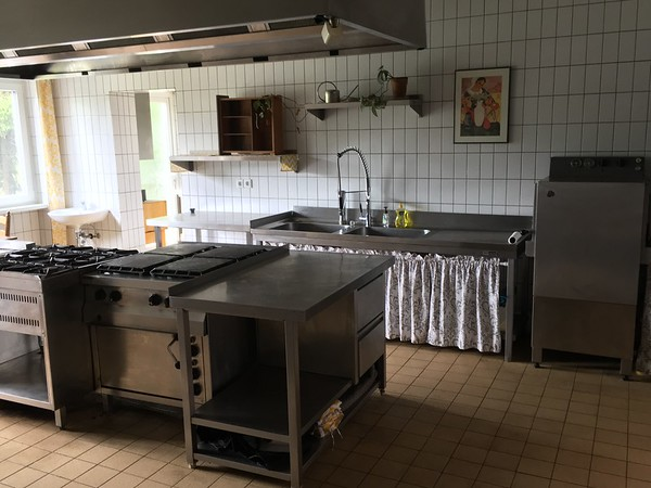 Gas burning stovetops, deep oven, two large basins at the sink, restaurant style dishwasher, hand washing sink, a lot of counter space.