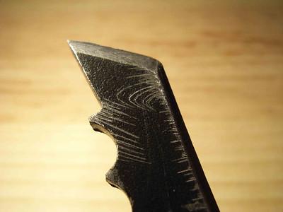 Lame neuve Simond vue de profil: Pointe piquante, Alésage de base au niveau du nez, premières dents de même épaisseur que la pointe aux bords bien francs ( excellente tenue en glace mais désancrage plus difficile ).