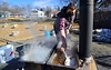 Hannah Tustin removes some of the debris from the boiling sap at the Oak Grove Elementary School, in Brattleboro, Vt., on Tuesday, March 23, 2021.