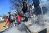 Tara Davis, the chair for the Parent Teacher Organization at Oak Grove Elementary, ladles some sap as her children watch during a sugaring demonstration on Tuesday, March 23, 2021.