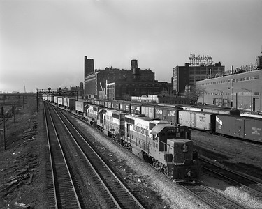 2010.030.09.1.015--lee hastman 4x5 neg--ICRR--EMD diesel locomotive 3041 on northbound piggyback freight train crossing over to St Charles Air Line approach at 22nd St--Chicago IL--late 1960s
