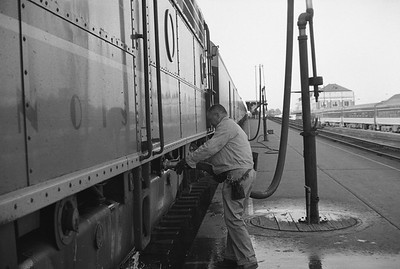 2010.030.05.9.030--lee hastman 35mm neg--ICRR--worker fueling diesel locomotive on Panama Ltd passenger train station stop at Champaign IL--c1965 0000