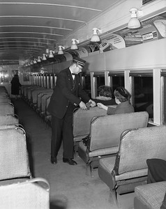2010.030.05.9.008--lee hastman 4x5 neg--ICRR--passenger conductor Al Williams taking tickets in commuter coach on South Chicago line--Chicago IL--1964 1126