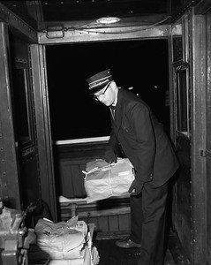 2010.030.05.9.011--lee hastman 4x5 neg--ICRR--passenger conductor Al Williams loading newspapers on commuter coach train 603--location unknown--1964 1203