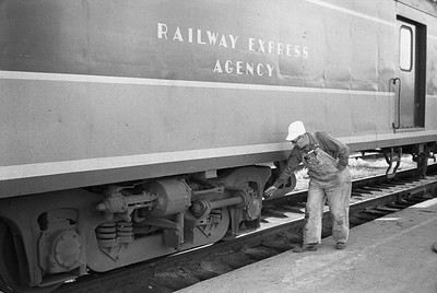 2010.030.05.9.032--lee hastman 35mm neg--ICRR--crew inspecting Panama Ltd passenger train during station stop at Champaign IL--c1965 0000