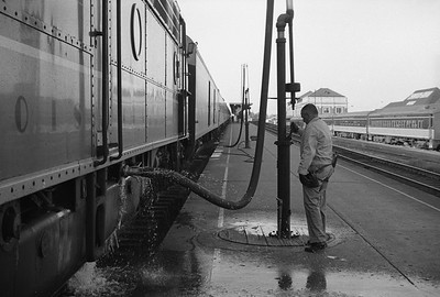 2010.030.05.9.029--lee hastman 35mm neg--ICRR--worker fueling diesel locomotive on Panama Ltd passenger train station stop at Champaign IL--c1965 0000