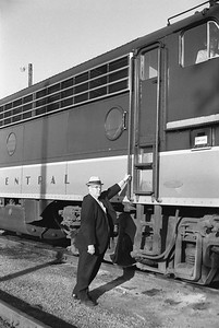 2010.030.05.9.036--lee hastman 35mm neg--ICRR--manager type posing with EMD diesel locomotive 4118 on Panama Ltd passenger train station stop at Champaign IL--c1965 0000