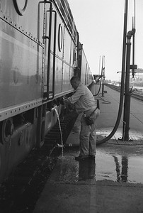 2010.030.05.9.031--lee hastman 35mm neg--ICRR--worker fueling diesel locomotive on Panama Ltd passenger train station stop at Champaign IL--c1965 0000