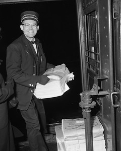 2010.030.05.9.010--lee hastman 4x5 neg--ICRR--passenger conductor Al Williams loading newspapers on commuter coach train 603--location unknown--1964 1203