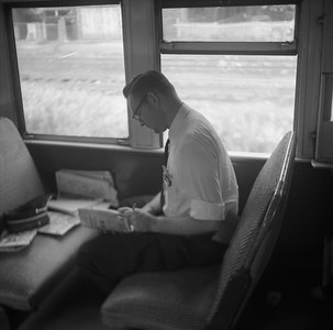 2010.030.05.9.007--lee hastman 120 neg--ICRR--passenger conductor Al Williams at work in commuter coach--location unknown--no date