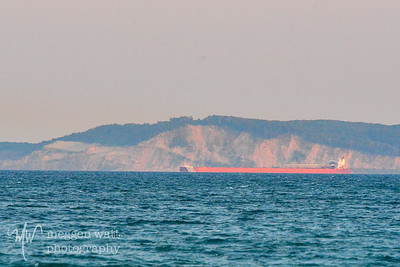 1,000-footer travels north, with Pyramid Point in the background. Light from the setting sun illuminates both.