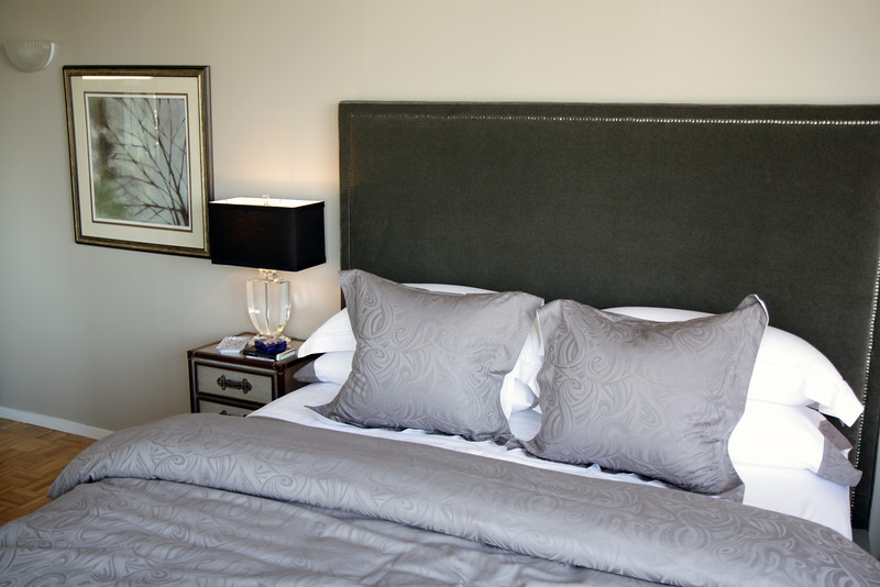 Lee Industries headboard and rails (S266TPT2T) upholstered in Flanders Coal and accented with hand hammered nail head trim and black walnut legs.<br /> A crystal urn table lamp sits atop the bedside chest with a mirrored finish and leather accents.  Artwork, Diffuse Branches.