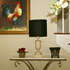 A colorful oil painting of a rooster on the wall, and a variety of small accessories from our shop atop a marble console table.
