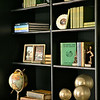 Our molten gold orb finials add interest to this bookcase. The Sagittarius Globe lends a more studious tone to the display.