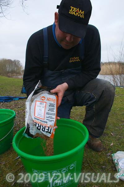 Will Raison pouring a bag of Sensas Terre De Somme into a groundbait mixing bucket. © 2009 Brian Gay