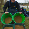 Angler Will Raison displays two contrasting groundbait mixes. The buckets contain the excess spare bait, the bowls contain measured quantities to form the initial feed. © 2009 Brian Gay