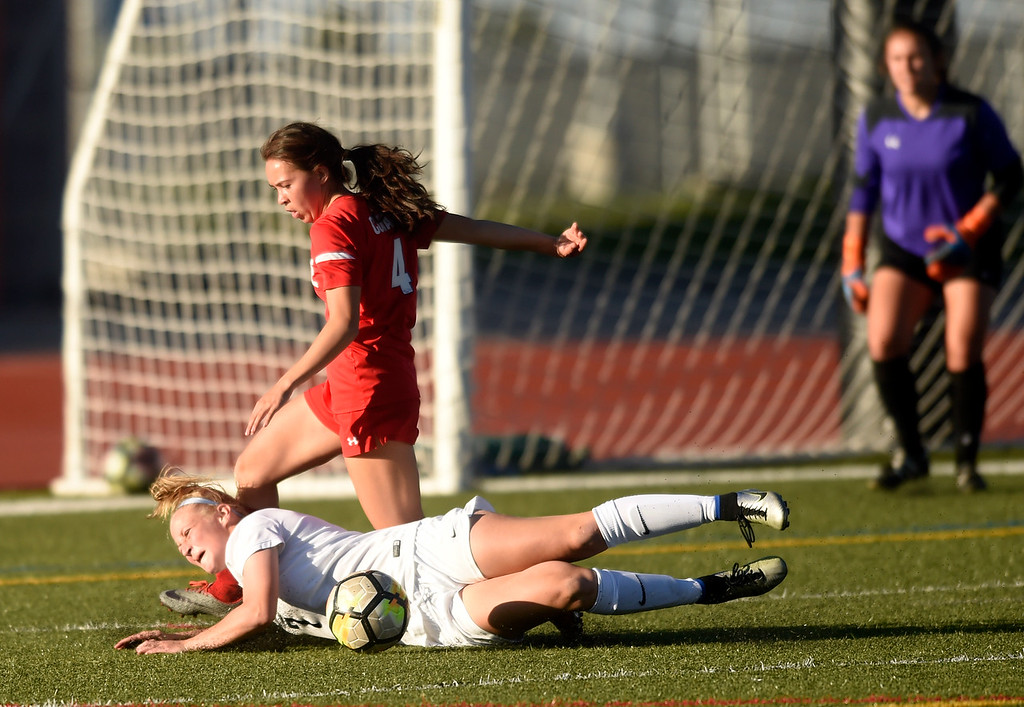 . Legacy High School\'s Kailey Maness goes down hard fighting for the ball with Kamaile Conant during a CHSAA first round playoff game against Heritage on Tuesday at the North Stadium in Westminster. More photos: BoCoPreps.com Jeremy Papasso/ Staff Photographer 05/08/2018
