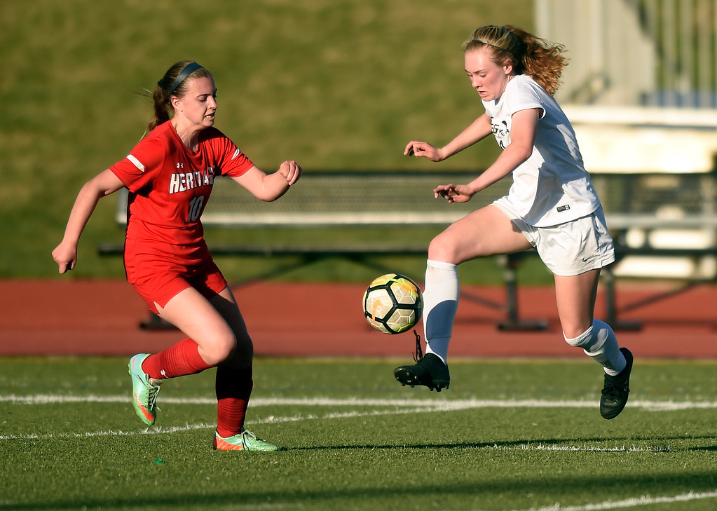 . Legacy High School\'s Nora Spuler moves the ball past Kelsey Harry during a CHSAA first round playoff game against Heritage on Tuesday at the North Stadium in Westminster. More photos: BoCoPreps.com Jeremy Papasso/ Staff Photographer 05/08/2018