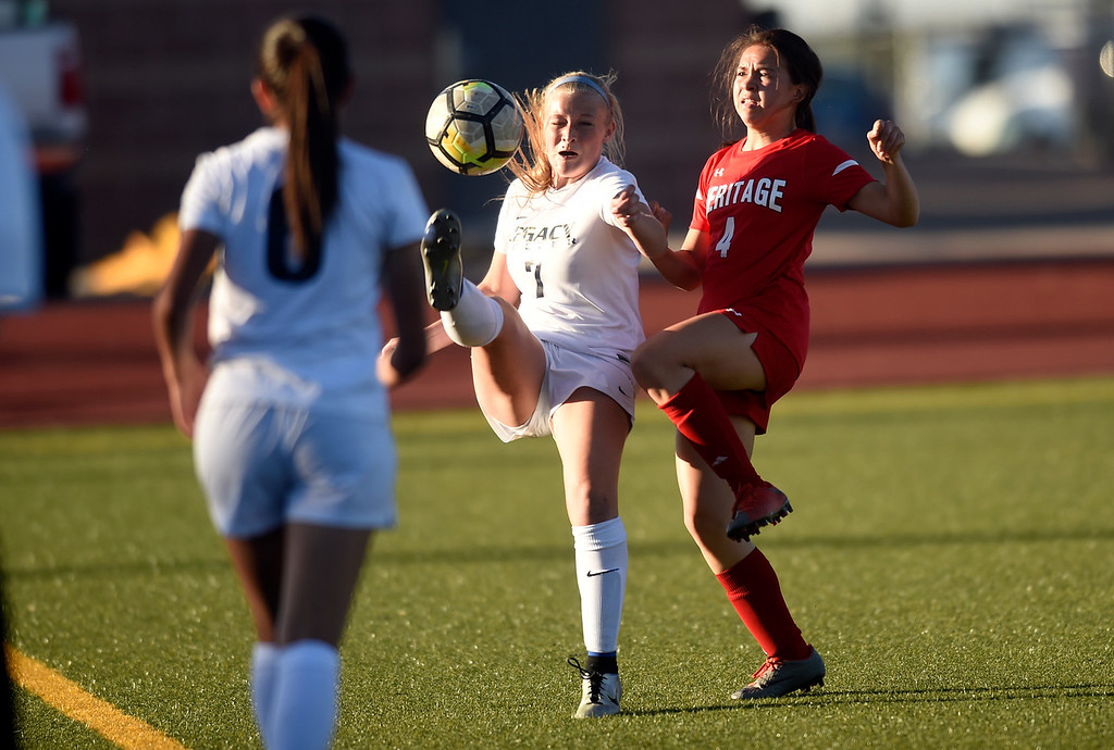 . Legacy High School\'s Kailey Maness stops a ball in front of Kamaile Conant during a CHSAA first round playoff game against Heritage on Tuesday at the North Stadium in Westminster. More photos: BoCoPreps.com Jeremy Papasso/ Staff Photographer 05/08/2018