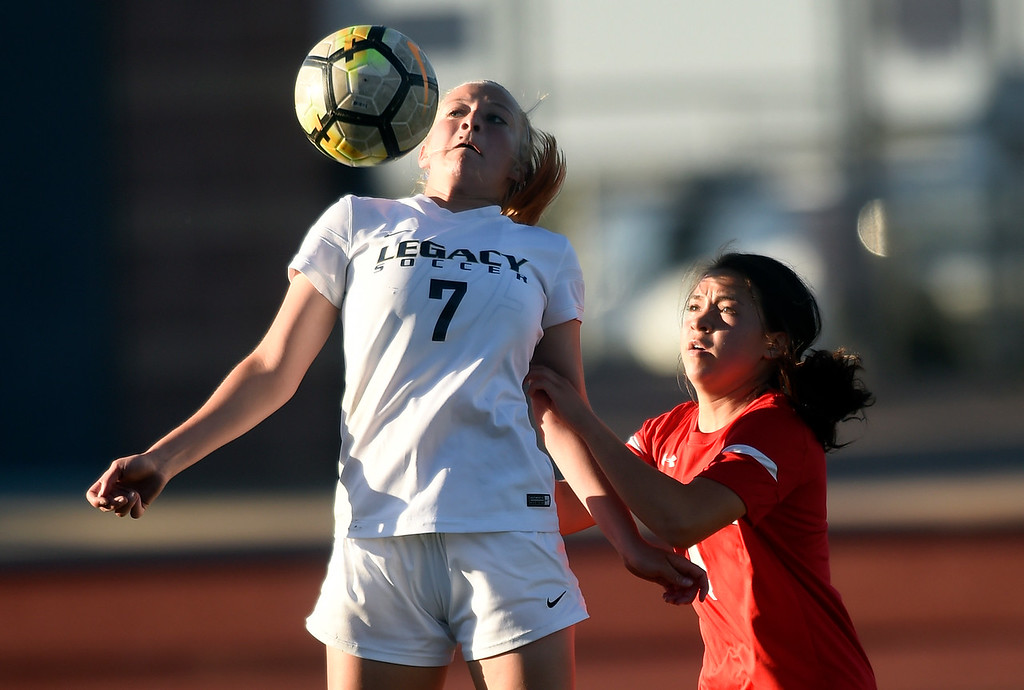 . Legacy High School\'s Kailey Maness stops a ball over Kamaile Conant during a CHSAA first round playoff game against Heritage on Tuesday at the North Stadium in Westminster. More photos: BoCoPreps.com Jeremy Papasso/ Staff Photographer 05/08/2018
