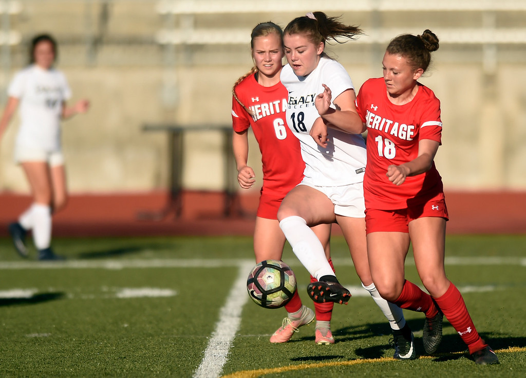 . Legacy High School\'s Alexis Gaffney moves the ball past Cailey Schmitt during a CHSAA first round playoff game against Heritage on Tuesday at the North Stadium in Westminster. More photos: BoCoPreps.com Jeremy Papasso/ Staff Photographer 05/08/2018