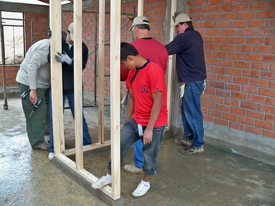 Oldest son Juan (14) helping volunteers set a wall where his mother, Domatilda, had just swept and cleaned so the wall could be placed in position. R.Abel