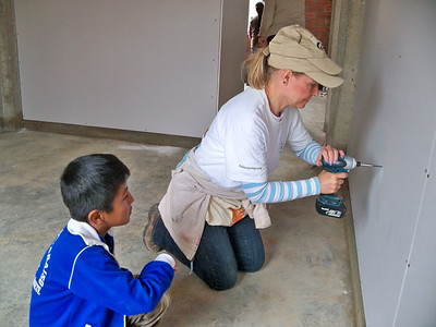 Youngest son Hector (8) helps volunteer Chris from Missouri install drywall by handling her screws. R.Abel
