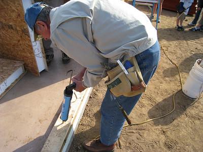 Millard Fuller caulks bottom plate. lcf