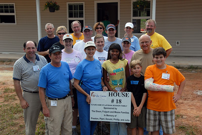 Linda Fuller, David Snell and Bill Scott pose with Lakishia Booker and all the volunteers who sponsored and helped build her house. cl  crl