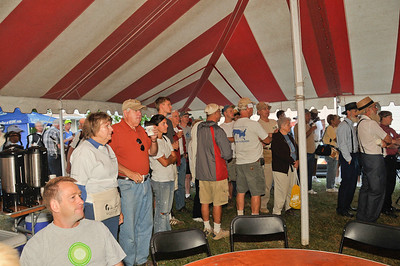 09 09-06 With the coffee brewing, announcements and devotions begin under the tent at 7:15 before construction work begins. Giving honor to God.   mlj