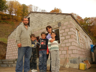 Family standing beside their new home in Armenia.