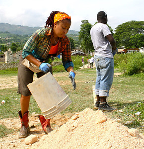 Kimberly Lacy unloads a bucket of sand, which will be used later for concrete.
