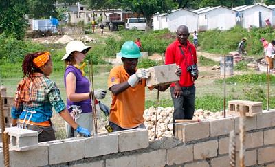 The group lays bricks.