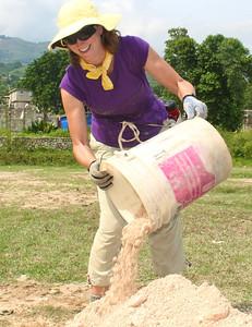 Renee Concilla unloads a bucket of sand.