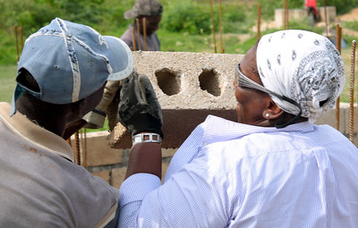 Donna Fitzgerald lays bricks with a little help from a member of the Haitian labor force.