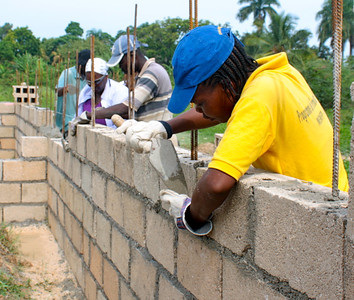 The group works on laying bricks and mortar.