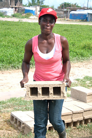 Kerline Jacques lifts a brick that will be part of her future home.