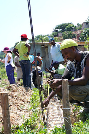 The Haitian labor force lowers metal structures into the foundation.