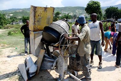The Haitian labor force prepares the concrete mixer.