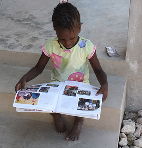 The daughter of a Fuller Center homeowner sits on the porch of her home and enjoys a magazine.
