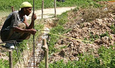 A member of the Haitian labor force measures the foundation.