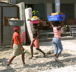 Everyday street life in Haiti – women carry baskets on their heads.
