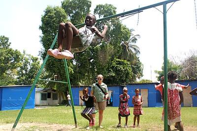 Team members help push the orphan girls on the swing set.