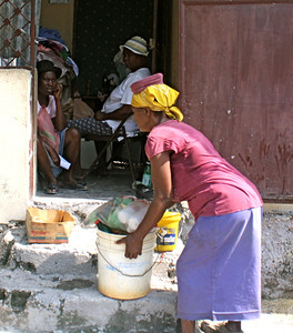 Everyday life in Haiti – a woman gets ready to put a bucket on her head.