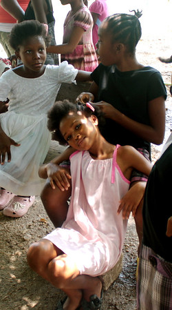 Orphan girls braid each others hair.