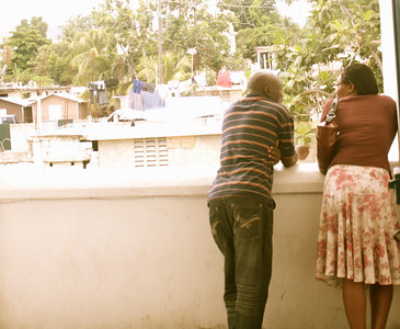 A Haitian man and woman look out over the neighborhood.