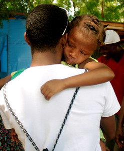 A Haitian orphan is comforted.