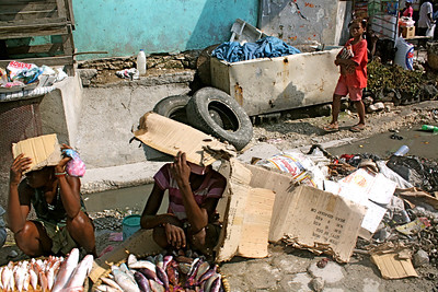 Street vendors shade themselves from the hot Haitian sun.