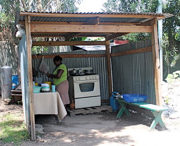 A woman cooks in an open kitchen.